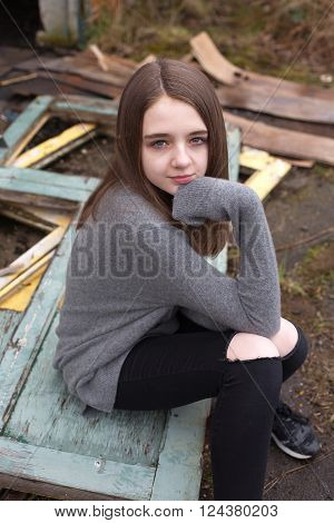 Pretty young teenage girl sitting on some old doors outside a derelict building