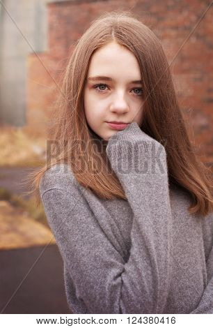 Pretty young teenage girl huddling in her jumper with a derelict building in the background