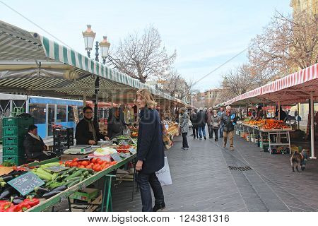NICE FRANCE - FEBRUARY 03; Large French green market Cours Saleya with people walking around and buying food in Nice France - February 03 2016: Open air market overflown with fresh cheese herbs fruit and vegetables.