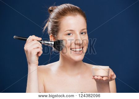 Smiling woman applying tonal cream over blue background