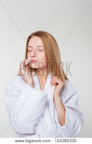 Woman in bathrobe cleaning face with cotton pad isolated on a white background