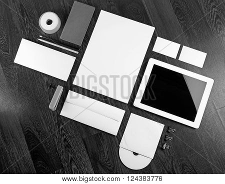 Photo of blank corporate identity template on dark wooden background. Blank stationery for design presentations and portfolios. ID template. Black and white image.
