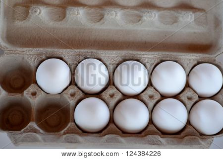Eggs lined up in a grey cardboard carton.