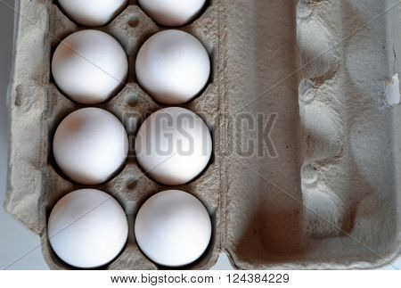 White Eggs in Cardboard Carton. Close-up from above.