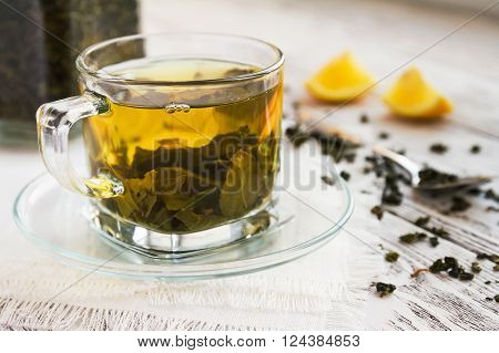 green tea with lemon and spoon on a rustic background