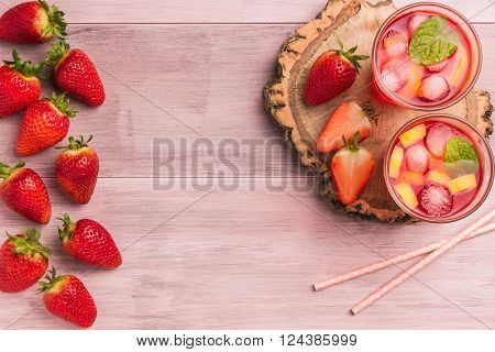 Refreshing summer drink with strawberry, lemon and ice in glasses on the vintage wooden table. Top view with copy space.