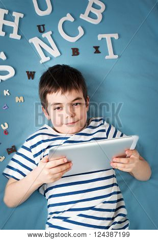seven years old child lying with tablet and letters on blue background