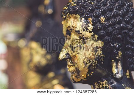 Closeup of Buddha statue gilded in the measure