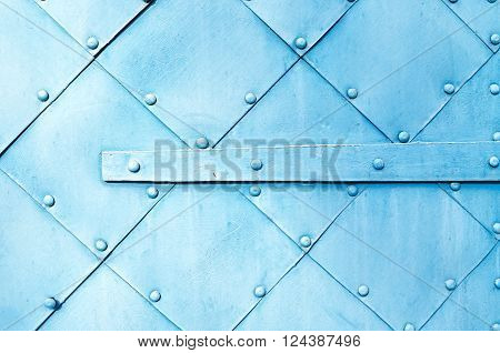 Metal light blue surface of old hammered metal plates with rivets and architectural details on them. Metal industrial background.