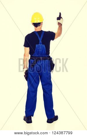 Repairman wearing hard hat pointing up
