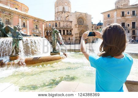 Tourist taking travel picture with phone of Cathedral in Valencia summer holidays. Unrecognizable female young adult enjoying Spanish vacations in blue t-shirt.