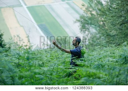 Hiker looking for his GPS signal on a smartphone disoriented in lush woodlands trying to find a way out. Orientation activity in nature concept.