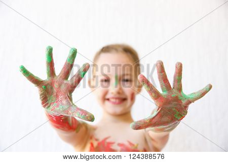 Little girl showing her hands covered in finger paint after painting a picture and her body with it. Sensory play permissive upbringing fun childhood concept selective sharpness.