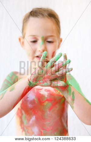 Little girl with hands covered in finger paint after painting a picture and her body with it. Tactile play, innovative learning, permissive upbringing, fun childhood concept, blur.