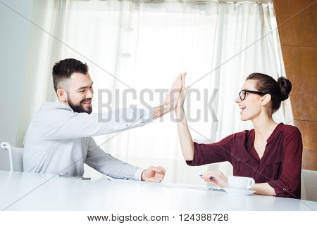 Two happy successful young businesspeople sitting and giving high five on the meeting