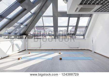Gym for fitness exercises. Mats and supporting blocks for yoga are on the floor. The room is flooded with sunlight from day oknon.