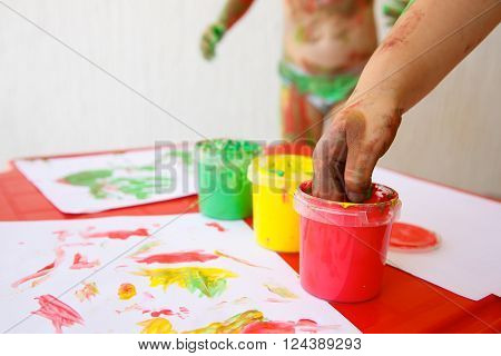 Child dipping fingers in washable non-toxic finger paints painting a drawing. Sensory play creativity fun childhood concept.