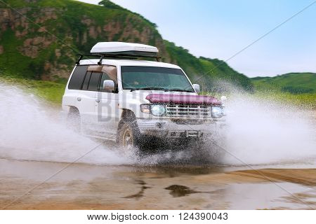KHASAN RUSSIA - JULY 25 2015: Mitsubishi Pajero moving fast by water making lots of splashes