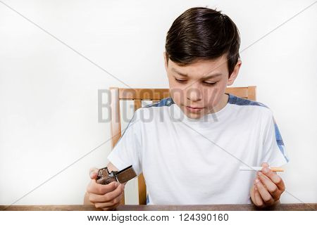 Young boy thinking about smoking a cigarette holding a lighter