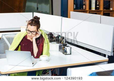 Sad cute young businesswoman in blanket working with laptop and feeling cold in office
