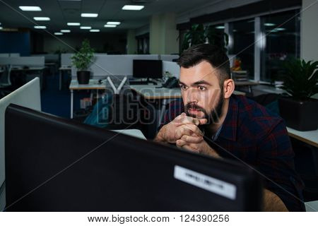 Handsome bearded young businessman sitting on workplace and working late