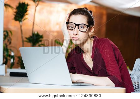 Exhausted tired young businesswoman in glasses sitting and using laptop on workplace
