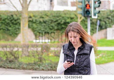 Single Woman Walking And Looking Down At Phone