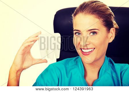 Female dentist holding tooth model and sitting behind the desk