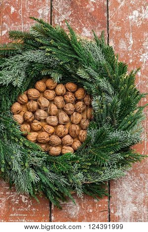 Christmas advent wreath filled with nuts on wooden table
