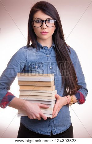 Young woman wearing nerd eyeglasses and holding stack of books