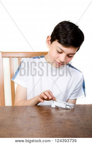 Young boy taking a cigarette from a packet