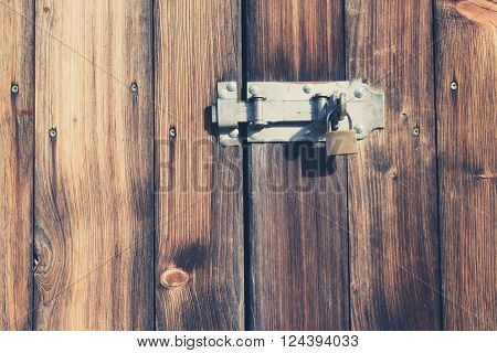 old wooden door with padlock and metal latch - vintage look