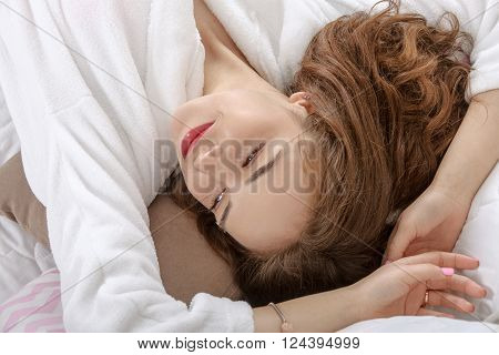 Girl woke up in a white bed in the morning. She is dressed in a white robe, her eyes closed and she lies on her back throwing her hands behind her head. Concept: lifestyle, health and beauty.