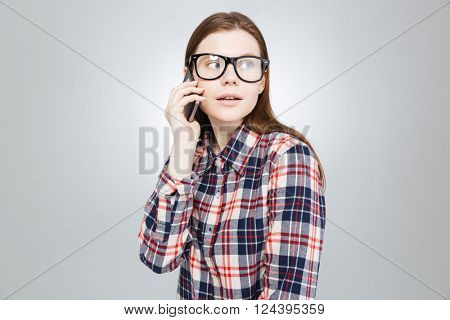 Cute lovely teenage girl in plaid shirt and glasses talking on cell phone