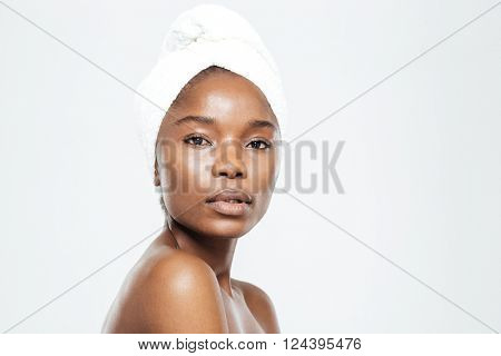 Beautiful afro american woman with towel on head looking at camera isolated on a white background