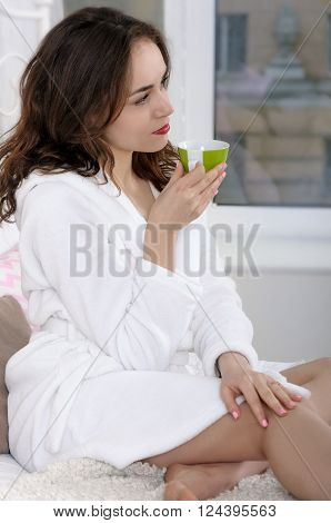 Girl woke up in the morning and drink coffee. She sits on the bed, holding a cup and looking out the window. Concept: lifestyle, health and beauty.