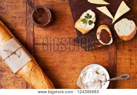 Savory and sweet snack with French baguette on a wooden table, top view