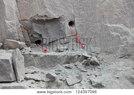 Preparation for explosive works: drilled rocks stuffed with explosives and ignition transmission line
