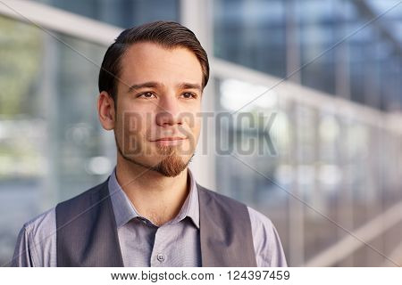 Head and shoulders portrait of a handsome young businessman standing in a city with reflective glass windows behind him, and looking away with a positive and optimistic expression