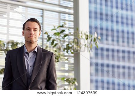 Portrait of a handsome young businessman with an optimistic expression, standing outside in a city with high-rise office buildings behind him and the delicate green leaves of a sidewalk plant