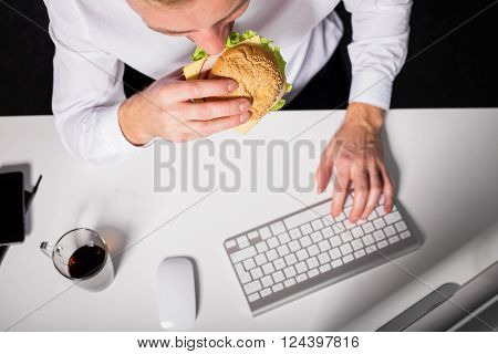 Man eating unhealthy lunch while working in the office