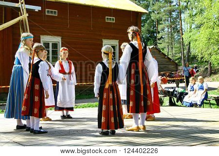 HELSINKI FINLAND - JUNE 20 2012: Unidentified dancers in folklore ensemble in traditional folk costumes at midsummer day festival. For editorial use only.