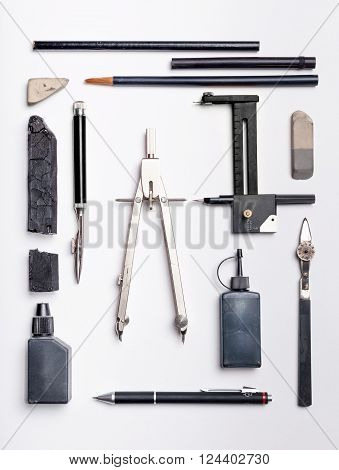 Flat lay of black drawing tools and supplies on white paper sheet