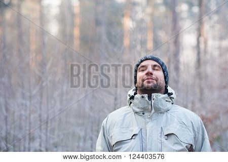 Young man in warm clothing standing outdoors on a cold winter's day, leaning back and closing his eyes to take in a deep breath in a peaceful forest with white frost on the plants