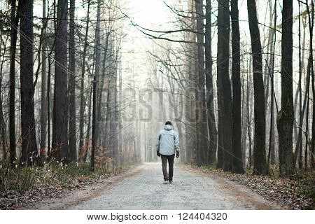Rearview full length shot of a man walking away from the camera down a road through a forest in winter
