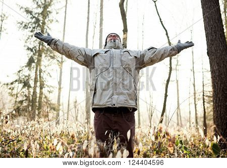 Man standing in a forest on a cold winter day, wearing warm clothing, lifting his arms up and closing his eyes to breath in the fresh winter air of a sunlit forest
