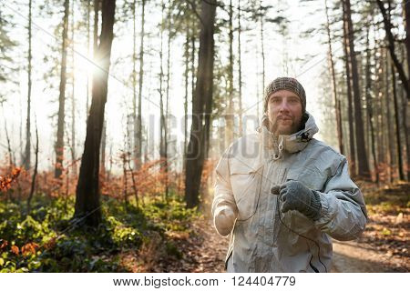 Man wearing warm clothing while jogging on a nature trail in a sunlit forest, on a cold winter morning with his breath making steam in the sunlight