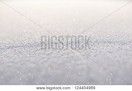 Nature image with no people of fine snow shot with differential focus to show the delicate crystals and the tiny sparkles of the individual particles, shining in the sun