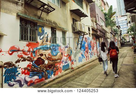 HONG KONG, CHINA - FEB 12: Two women walking at narrow street with street art grafitti in big city on February 12, 2016. There are 1223 skyscrapers in Hong Kong.
