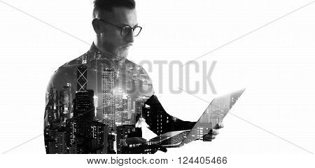 Double exposure bearded businessman wearing black shirt and glasses.Banker holding contemporary notebook hands, online banking.Isolated white, modern skyscraper city at night background